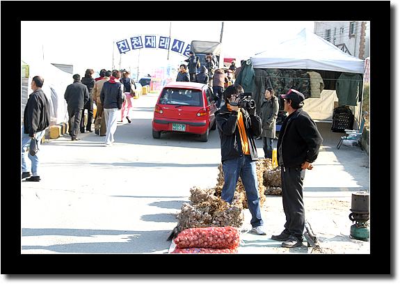 재래시장을 담는 카메라와 인터뷰중인 상인
